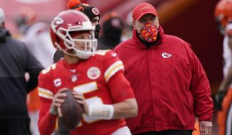 FILE - In this Sunday, Jan. 17, 2021 file photo, Kansas City Chiefs head coach Andy Reid, right, watches quarterback Patrick Mahomes warm up before an NFL divisional round football game against the Cleveland Browns in Kansas City. On Feb. 7, 2021, the Kansas City Chiefs will be the latest franchise to attempt winning successive Super Bowls when they take on the Buccaneers. In Tampa, of all places. Against Tom Brady, of all people. Only  twice since the Patriots pulled off the last repeat in the 2003 and 2004 season has a champion gotten back to the big game. Seattle failed in 2014  against New England, no less; remember Malcolm Butler's goal-line interception?  and the Patriots in 2017, the Super Bowl featuring the Philly Special. (AP Photo/Charlie Riedel, File)