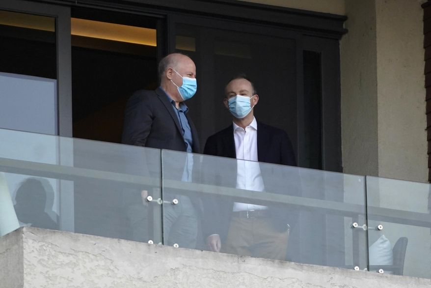 Members of the World Health Organization team chat on a hotel room balcony in Wuhan in central China's Hubei province on Friday, Jan. 29, 2021. The World Health Organization team of researchers emerged from their hotel Thursday for the first time since their arrival in the central Chinese city of Wuhan to start searching for clues into the origins of the COVID-19 pandemic. (AP Photo/Ng Han Guan)