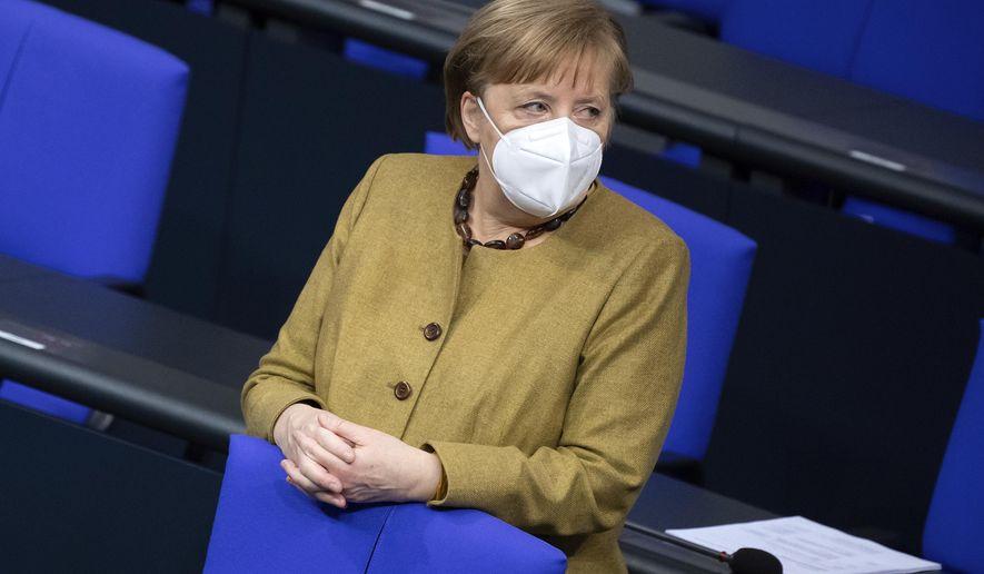 German Chancellor Angela Merkel attends a meeting of the German Federal Parliament, Bundestag, at the Reichstag building in Berlin, Germany, Thursday, Jan. 28, 2021. (Bernd von Jutrczenka/dpa via AP)