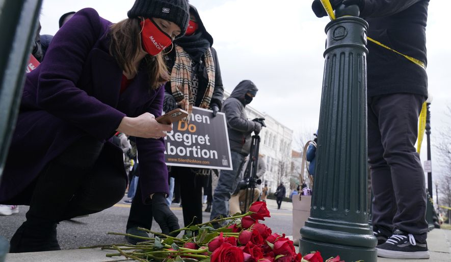Catherine Glenn Foster, President and Chief Executive Officer of Americans United for Life, left, places a rose on the sidewalk on the back side of the Supreme Court during the 48th Annual March for Life in Washington, Friday, Jan. 29, 2021. (AP Photo/Susan Walsh)