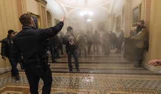 Smoke fills the walkway outside the Senate Chamber as supporters of President Donald Trump are confronted by U.S. Capitol Police officers inside the Capitol in Washington. (AP Photo/Manuel Balce Ceneta, File)