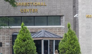 FILE - In this Aug. 13, 2019 file photo, an employee checks a visitor outside the Metropolitan Correctional Center in New York. The warden brought in to clean up the embattled federal jail where Jeffrey Epstein killed himself has abruptly stepped down after a year-long tenure marred by the rampant spread of coronavirus, inmates complaints about poor conditions, a gun smuggled into the facility, and an inmate's death. (AP Photo/Mary Altaffer, File)