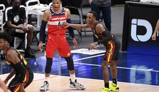 Washington Wizards guard Russell Westbrook (4) stands on the court next to Atlanta Hawks guard Rajon Rondo, right, during the first half of an NBA basketball game, Friday, Jan. 29, 2021, in Washington. (AP Photo/Nick Wass)