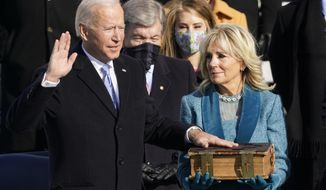 """FILE - In this Wednesday, Jan. 20, 2021 file photo, Joe Biden is sworn in as the 46th president of the United States by Chief Justice John Roberts as Jill Biden holds the Bible during the 59th Presidential Inauguration at the U.S. Capitol in Washington. On Friday, Jan. 29, 2021, The Associated Press reported on stories circulating online incorrectly asserting Biden swore on a """"Masonic/Illuminati"""" Bible during his inauguration. It is a Douay-Rheims Bible, an English translation of a Latin Bible, which has been in the Biden family since the 1890s. Robert Miller, professor of biblical studies at The Catholic University of America, says, """"Nothing even vaguely Masonic would have been anywhere near these Bibles. … Same thing for the 'Illuminati,' to the extent that such a thing existed: repeatedly condemned by the Popes and certainly coming nowhere into contact with Catholic Bibles."""" (AP Photo/Andrew Harnik)"""