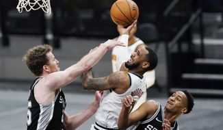 Denver Nuggets guard Monte Morris, center, shoots over San Antonio Spurs center Jakob Poeltl, left, and San Antonio Spurs guard Devin Vassell, right, during the second half of an NBA basketball game in San Antonio, Friday, Jan. 29, 2021. (AP Photo/Eric Gay)