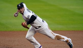 In this Sept. 11, 2020, file photo, Colorado Rockies third baseman Nolan Arenado throws to first during the first inning of a baseball game against the Los Angeles Angels in Denver. A person familiar with the swap tells The Associated Press that the St. Louis Cardinals have agreed to acquire All-Star third baseman Arenado from the Rockies in a trade needing approvals before it can be finalized. (AP Photo/David Zalubowski, File)
