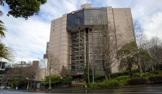 The Grand Millenium hotel, a managed isolation facility is seen in central Auckland, New Zealand, July, 16, 2020. A traveler and a worker at the quarantine hotel started passing each other notes, including one written on the back of a face mask. Then he delivered a bottle of wine she'd ordered to her room. When he didn't return 20 minutes later, a security manager sent to investigate found the pair together in what authorities are describing as an inappropriate encounter, one in which physical distancing wasn't maintained. (Sylvie Whinray/New Zealand Herald via AP)