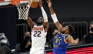 Phoenix Suns center Deandre Ayton (22) shoots past Golden State Warriors forward Kevon Looney (5) during the first half of an NBA basketball game, Thursday, Jan. 28, 2021, in Phoenix. (AP Photo/Matt York)