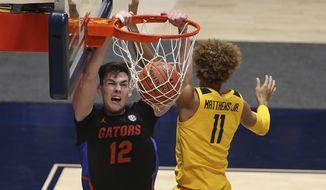 Florida forward Colin Castleton (12) dunks on West Virginia forward Emmitt Matthews Jr. (11) during the second half of an NCAA college basketball game Saturday, Jan. 30, 2021, in Morgantown, W.Va. (AP Photo/Kathleen Batten)