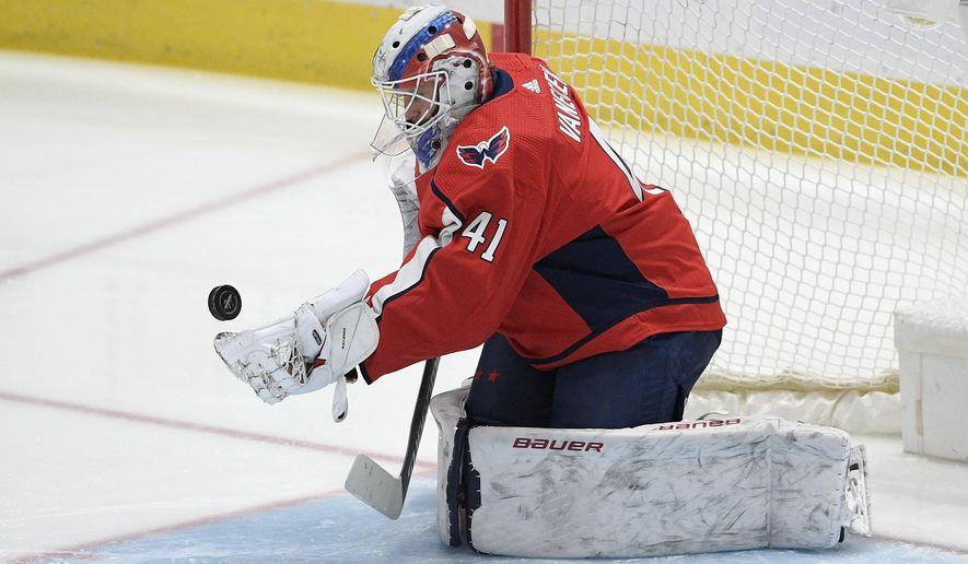 Washington Capitals goaltender Vitek Vanecek (41) stops the puck during the first period of an NHL hockey game against the Boston Bruins, Saturday, Jan. 30, 2021, in Washington. (AP Photo/Nick Wass)