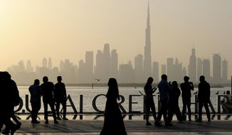 People enjoy their weekend with the view of city skyline and the world tallest tower, Burj Khalifa, in Dubai, United Arab Emirates, Friday, Jan.29, 2021. (AP Photo/Kamran Jebreili)