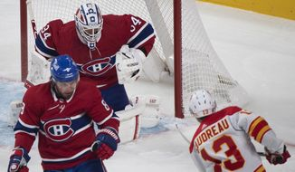Calgary Flames' Johnny Gaudreau (13) scores against Montreal Canadiens goaltender Jake Allen, top, as Canadiens' Ben Chiarot (8) defends during first-period NHL hockey game action in Montreal, Saturday, Jan. 30, 2021. (Graham Hughes/The Canadian Press via AP)