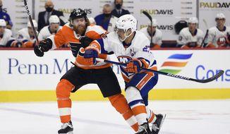 Philadelphia Flyers' Jakub Voracek, left, works for position against New York Islanders' Anders Lee during the first period of an NHL hockey game Saturday, Jan. 30, 2021, in Philadelphia. (AP Photo/Derik Hamilton)