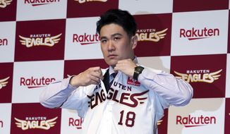 Former New York Yankees pitcher Masahiro Tanaka puts on his new uniform for a photo session during a news conference Saturday, Jan. 30, 2021 in Tokyo. Tanaka returned to Japan to rejoin the Rakuten Golden Eagles in the Nippon Professional Baseball League. (AP Photo/Eugene Hoshiko)