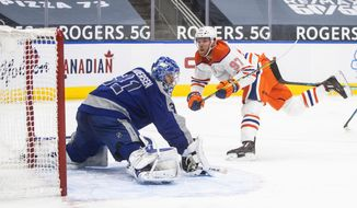 Edmonton Oilers' Connor McDavid (97) scores on Toronto Maple Leafs goalie Frederik Andersen (31) during the second period of an NHL game in Edmonton, Alberta, on Saturday, Jan. 30, 2021. (Jason Franson/The Canadian Press via AP)
