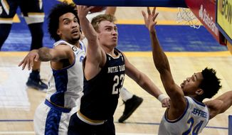Notre Dame's Dane Goodwin, center, shoots as he gets between Pittsburgh's William Jeffress (24) and Justin Champagnie during the first half of an NCAA college basketball game, Saturday, Jan. 30, 2021, in Pittsburgh. (AP Photo/Keith Srakocic)