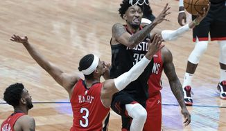 Houston Rockets center Christian Wood (35) shoots past New Orleans Pelicans guard Josh Hart (3) and forward Zion Williamson (1) during the second quarter of an NBA basketball game in New Orleans, Saturday, Jan. 30, 2021. (AP Photo/Derick Hingle)