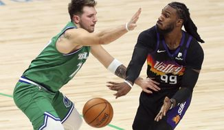 Dallas Mavericks guard Luka Doncic (77) defends against Phoenix Suns forward Jae Crowder (99) during the first half during an NBA basketball game Saturday, Jan. 30, 2021, in Dallas. (AP Photo/ Richard W. Rodriguez)