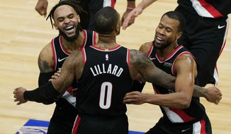 Portland Trail Blazers guard Damian Lillard (0) celebrates with guards Gary Trent Jr., left, and Rodney Hood after making the winning three-point basket during the second half of an NBA basketball game against the Chicago Bulls in Chicago, Saturday, Jan. 30, 2021. (AP Photo/Nam Y. Huh)