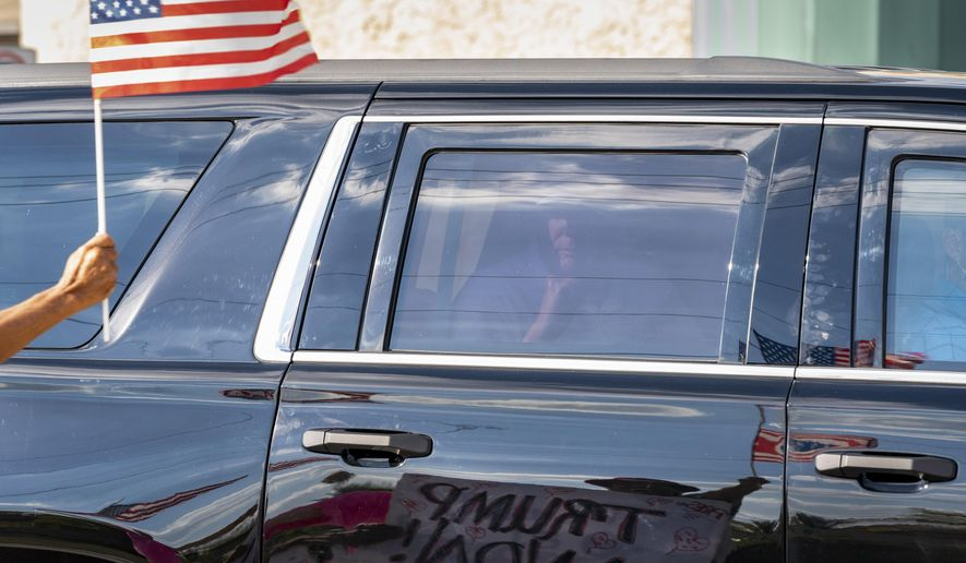 Former President Donald Trump passes supporters while traveling in his motorcade in West Palm Beach, Fla., on Wednesday, Jan. 27, 2021, on his way to Mar-a-Lago in Palm Beach. (Greg Lovett/The Palm Beach Post via AP)