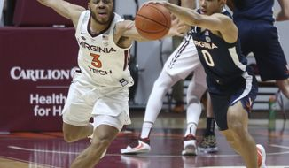 Virginia Tech's Wabissa Bede, left, and Virginia's Kihei Clark, right, compete for a tipped ball during the first half of an NCAA college basketball game Saturday, Jan. 30, 2021, in Blacksburg, Va. (Matt Gentry/The Roanoke Times via AP, Pool)