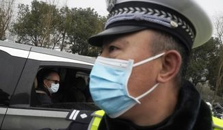 Peter Ben Embarek of the World Health Organization team passes by a Chinese police officer as he leaves in a convoy from the Baishazhou wholesale market on the third day of field visit in Wuhan in central China's Hubei province on Sunday, Jan. 31, 2021. (AP Photo/Ng Han Guan)