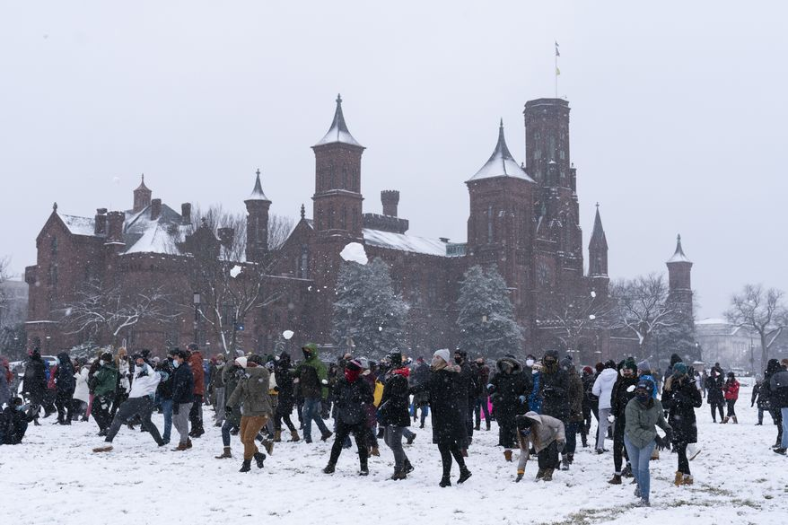 People throw snowballs during a snowball fight, organized by the Washington DC Snowball Fight Association, near the Smithsonian Castle on the National Mall, Sunday, Jan. 31, 2021, in Washington. (AP Photo/Alex Brandon)