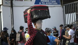A passenger, wearing protective face gear amid the new coronavirus pandemic, arrives at a long-distance bus terminal, in Lima, Peru, Saturday, Jan. 30, 2021. Hundreds of people are traveling to their provinces of origin before a strict two-week quarantine begins Sunday in various regions of the country as a measure to curve the spread of COVID-19. (AP Photo/Rodrigo Abd)