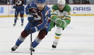 Colorado's Tyson Jost (17) handles the puck against Minnesota Wild's Nick Bjugstad (27) in the second period of an NHL hockey game Sunday, Jan. 31, 2021, in St. Paul, Minn. (AP Photo/Stacy Bengs)