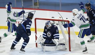 Vancouver Canucks' Nils Hoglander (36) and Tanner Pearson (70) celebrate Hoglander's goal against Winnipeg Jets goaltender Connor Hellebuyck (37) during the first period of an NHL hockey game Saturday, Jan. 30, 2021, in Winnipeg, Manitoba. (john Woods/The Canadian Press via AP)
