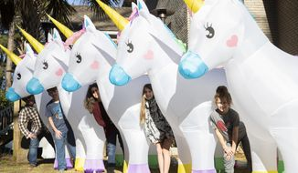 Ed and Tracy McDonnell pose for a portrait with their inflatable unicorns at their home in Columbia, S.C. on Thursday, Jan. 14, 2021. The family placed the unicorns at friends homes across their neighborhood, and slowly brought them back to their own yard. (Joshua Boucher/The State via AP)