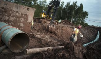 In this Aug. 21, 2017, file photo, workers make sure that each section of the Enbridge replacement Line 3 that is joined passes muster in Superior, Wisc. After President Joe Biden revoked Keystone XL's presidential permit and shut down construction of the long-disputed pipeline that was to carry oil from Canada to Texas, opponents of other pipelines hoped the projects they've been fighting would be next. (Richard Tsong-Taatarii /Star Tribune via AP) ** FILE **