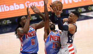 Washington Wizards guard Russell Westbrook, right, goes to the basket against Brooklyn Nets guard Kyrie Irving (11) and center DeAndre Jordan (6) during the first half of an NBA basketball game, Sunday, Jan. 31, 2021, in Washington. (AP Photo/Nick Wass) **FILE**