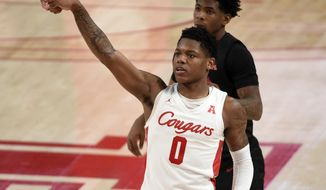 Houston guard Marcus Sasser (0) watches his 3-point basket during the second half of an NCAA college basketball game against SMU, Sunday, Jan. 31, 2021, in Houston. (AP Photo/Eric Christian Smith)