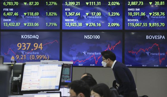 A currency trader watches monitors at the foreign exchange dealing room of the KEB Hana Bank headquarters in Seoul, South Korea, Monday, Feb. 1, 2021. Asian stock markets gained Monday after coronavirus vaccine maker AstraZeneca agreed to increase supplies to Europe amid rising worries about the disease. (AP Photo/Ahn Young-joon)