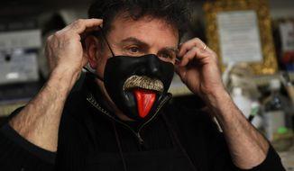 Venetian artisan carnival mask maker Gualtiero Dall'Osto wears one of his creations in his workshop in Venice, Italy, Saturday, Jan. 30, 2021. (AP Photo/Antonio Calanni)
