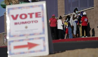 In this Nov. 3, 2020, file photo, people wait in line to vote at a polling place on Election Day in Las Vegas. (AP Photo/John Locher, File)  **FILE**