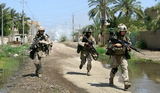 U.S. Marines from the 3rd Battalion, 8th Marine Regiment run through a street Wednesday, April 19, 2006, in Ramadi, 115 km (70 miles) west of Baghdad. (Associated Press) **FILE**
