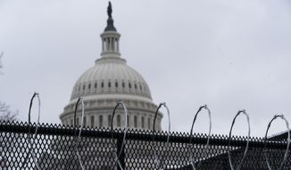 A anti-scaling fence topped with razor wire surrounds the U.S. Capitol, Monday, Feb. 1, 2021, in Washington. (AP Photo/Alex Brandon)