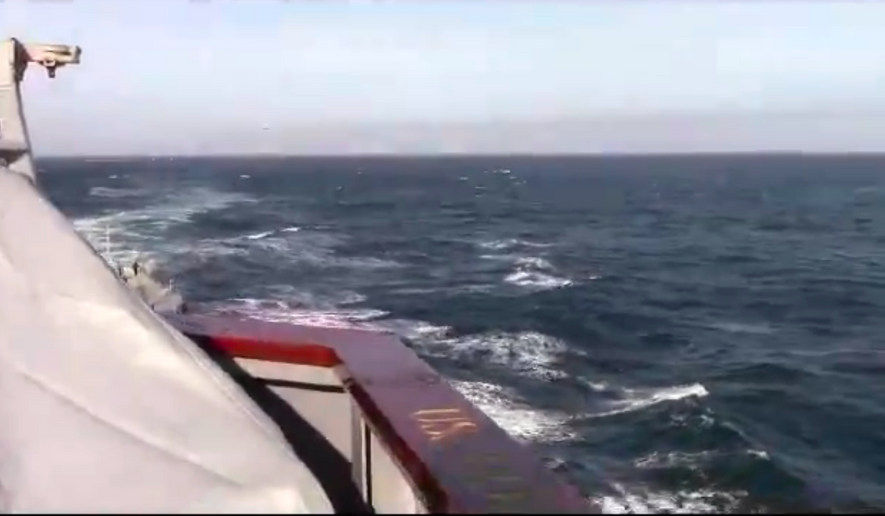 This screenshot from a U.S. Navy video shows a Russian jet (top left) approaching an American warship.