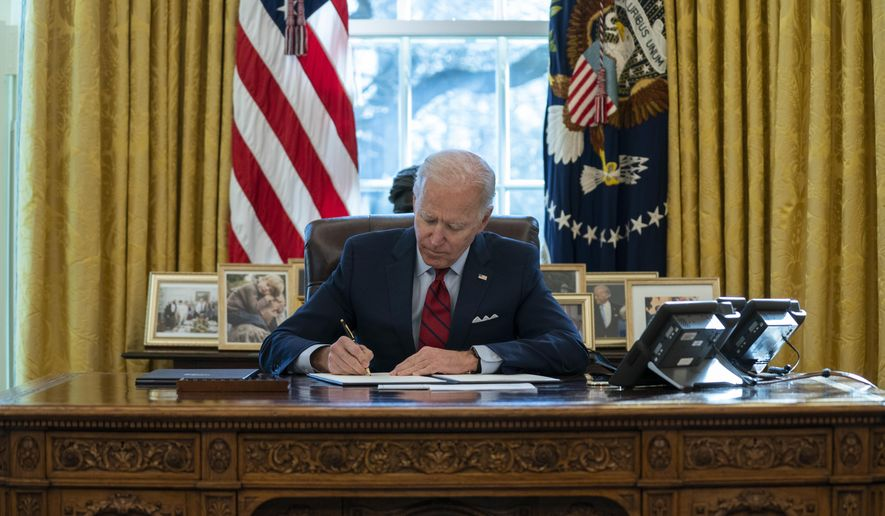In this Jan. 28, 2021, file photo President Joe Biden signs a series of executive orders on health care, in the Oval Office of the White House in Washington. A new Zogby poll shows Mr. Biden with a 56% approval rating, with even 30% of self-described conservatives approving of his job in office so far.  (AP Photo/Evan Vucci, File)  **FILE**