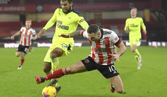Sheffield United's Billy Sharp challenges for the ball with Newcastle's DeAndre Yedlin during the English Premier League soccer match between Sheffield United and Newcastle United at the Bramall Lane stadium in Sheffield, England, Tuesday, Jan. 12, 2021. (Stu Forster/Pool via AP)