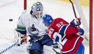 Montreal Canadiens left wing Artturi Lehkonen (62) is stopped by Vancouver Canucks goaltender Braden Holtby (49) during second-period NHL hockey game action Monday, Feb. 1, 2021, in Montreal. (Ryan Remiorz/The Canadian Press via AP)