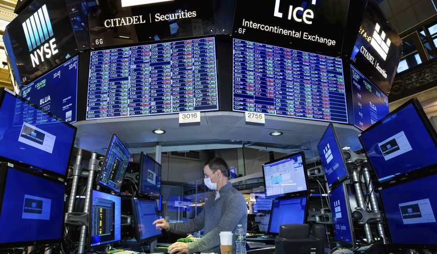 In this photo provided by the New York Stock Exchange, specialist Stephen Naughton works at a post on the trading floor, Monday, Feb. 1, 2021. The erratic trading in shares of underdog companies like GameStop that turned markets combustible last week appears to have migrated to commodities, sending silver prices surging to an eight-year high. (Nicole Pereira/New York Stock Exchange via AP)