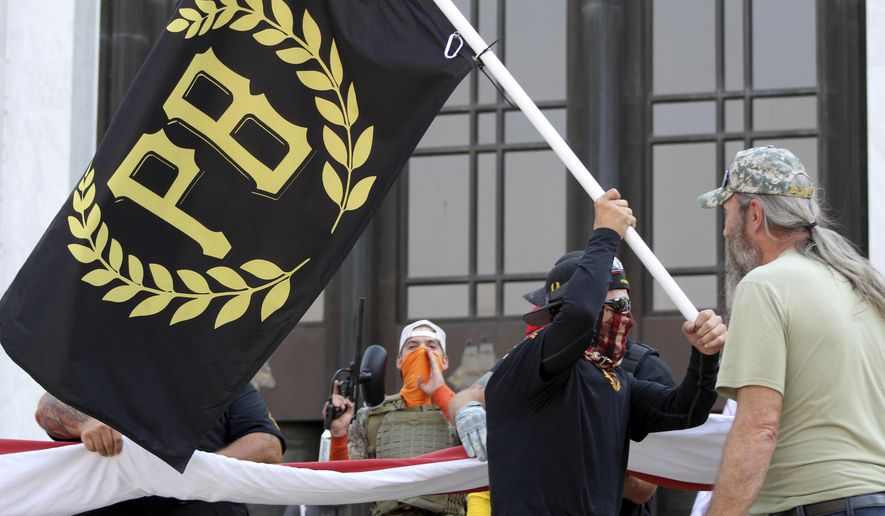 In this Sept. 7, 2020, file photo, a protester carries a Proud Boys banner, a right-wing group, while other members start to unfurl a large U.S. flag in front of the Oregon State Capitol in Salem, Ore. (AP Photo/Andrew Selsky, File)