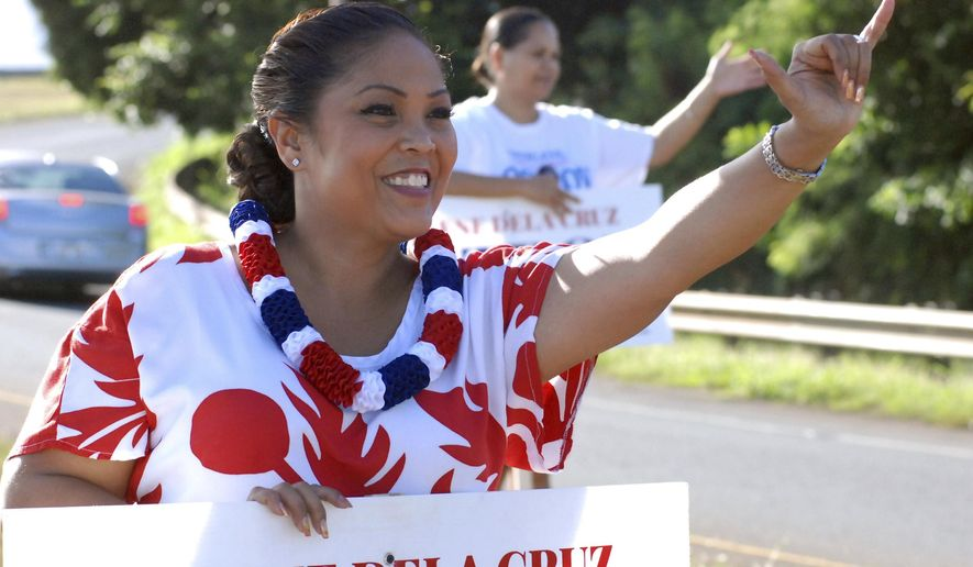 FILE - In this Nov. 2, 2016, file photo, Shirlene Ostrov, then-Republican candidate for Congress, waves to drivers at a highway intersection in Waipahu, Hawaii. The top official in the Hawaii Republican party has resigned a week after one of her top chairman posted pro-QAnon tweets on the GOP's official account.  Ostrov took full responsibility in the wake of the tweets posted Jan. 23, 2021, by Edwin Boyette, the communications chairman who resigned a day later. (AP Photo/Cathy Bussewitz, File)