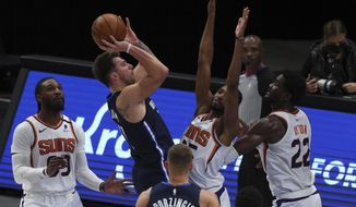 Dallas Mavericks guard Luka Doncic (77) shoots against Phoenix Suns forward Mikal Bridges (25) and center Deandre Ayton (22) in the first half during an NBA basketball game, Monday, Feb. 1, 2021, in Dallas. (AP Photo/ Richard W. Rodriguez)