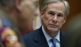 Texas Gov. Greg Abbott, right, takes part in a roundtable discussion on public safety and law enforcement, Thursday, Jan. 21, 2021, in Austin, Texas. (AP Photo/Eric Gay)