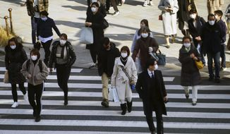People wearing protective masks to help curb the spread of the coronavirus walk along a pedestrian crossing Monday, Feb. 1, 2021, in Tokyo. The Japanese capital confirmed more than 390 new coronavirus cases on Monday. (AP Photo/Eugene Hoshiko)