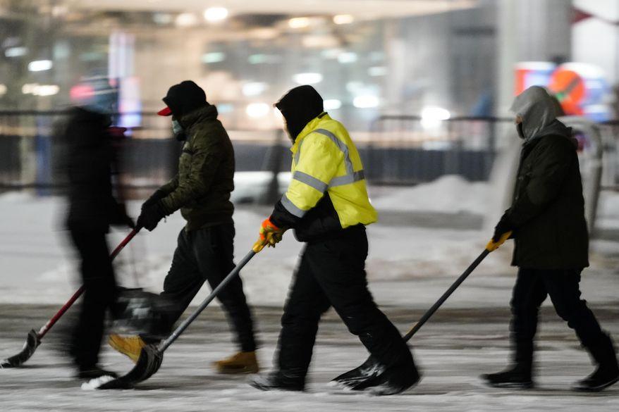Workers remove snow during a winter storm in Philadelphia, Monday, Feb. 1, 2021. (AP Photo/Matt Rourke)